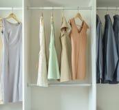 Mann und Frauenkleider, die an den Aufhängern in der Garderobe hängen Lizenzfreies Stockfoto