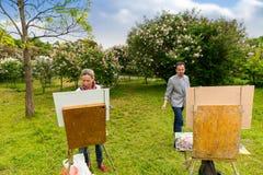 Mann- und Frauenmaler, die ihre Bilder auswerten Stockfotos