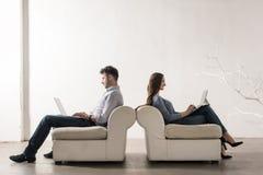 Mann- und Frauensitzen Rücken an Rücken im leeren Raum, der auf lapt arbeitet Stockfotografie