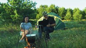 Mann- und Frauentouristen sitzen am Zelt und passen den Topf, über dem Feuer zu hängen auf und mit einem Laptop zu arbeiten stock video footage