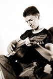 Mann und Gitarre am Stuhl lizenzfreies stockbild