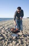 Mann und Grill auf Strand Lizenzfreies Stockfoto