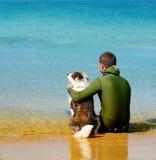 Mann und Hund, die im Wasser stationieren Lizenzfreies Stockbild