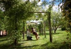 Mann- und Hundespielen umfasst unter einer Pergola von kletternden Rosen Stockbilder