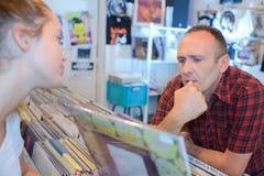 Mann und junge Dame, die Langspielplatten im Rekordshop betrachten Lizenzfreie Stockbilder