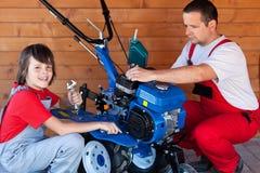 Mann und Junge, die eine Landwirtmaschine für Arbeit vorbereiten Lizenzfreies Stockbild