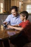 Mann und junger Junge auf Laptop Stockbilder