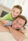 Mann und junger Junge, die beim Wohnzimmerlächeln sitzen stockbild