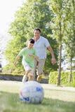 Mann und junger Junge, die draußen Fußball spielen Stockbilder