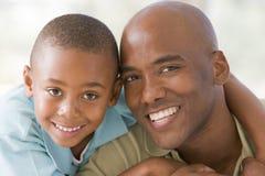 Mann und junger Junge umfassen und lächeln Stockfotos