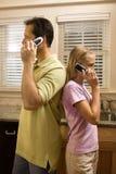 Mann und junges Mädchen an den Telefonen Stockbilder