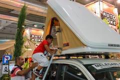 Mann und Kind, die Selbstzelt in der jährlichen Ausstellung des Reisemobils prüfen lizenzfreie stockbilder