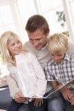 Mann und Kinder, die zusammen lesen Stockfoto