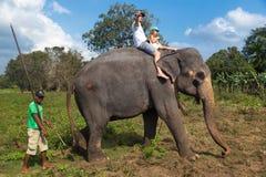 Mann- und Kinderreiten auf der Rückseite des Elefanten Lizenzfreies Stockfoto