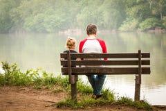 Mann-und Kleinkind-Mädchen auf Bank neben Fluss Lizenzfreie Stockfotografie