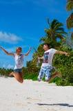 Mann und Mädchen, die auf den Strand springen Stockfoto