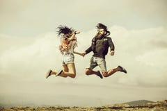 Mann und Mädchen springen hoch stockfoto