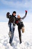 Mann und Mädchen stehen auf schneebedecktem Bereich und legen Fahrwerkbein dar Lizenzfreies Stockbild