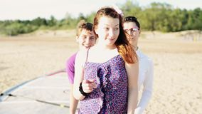 Mann- und Mädchentanz von der Rückseite eines anderen Mädchens auf Strand lächeln in camera Sonniger Tag stock video footage
