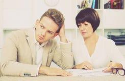 Mann und reife Frau sitzen bei Tisch Lizenzfreie Stockfotografie