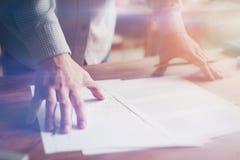 Mann und Schreibarbeit auf Holztisch Modernes Büro Handnahaufnahme Filmeffekt und Blendenfleckeffekt Lizenzfreies Stockfoto