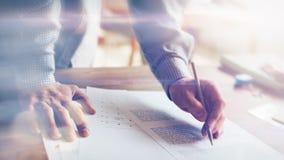 Mann und Schreibarbeit Dachbodenbüro Handnahaufnahme und -bleistift Filmeffekt und Blendenfleckeffekt Lizenzfreie Stockbilder