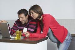 Mann und schwangere Frau, die das on-line-Einkaufen tun lizenzfreies stockfoto