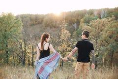 Mann und schwangere Frau, die Händchenhalten auf dem Hintergrund der wilden Natur, Herbst umarmen Mädchen und Junge küssen im Gar Lizenzfreie Stockfotografie