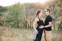 Mann und schwangere Frau, die Händchenhalten auf dem Hintergrund der wilden Natur, Herbst umarmen Mädchen und Junge küssen im Gar Stockbilder