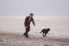 Mann und schwarzer Hund auf dem Strand Lizenzfreies Stockbild