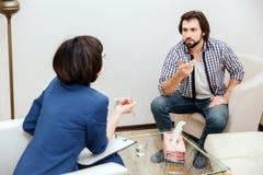 Mann und sein Doktor haben ein Gespräch Es ist sehr emotional Bärtiger Kerl bewegt seine Hand wellenartig Therapeut ist das Hande lizenzfreies stockfoto
