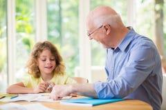 Mann und sein Enkelkind, welche die Hausarbeit nach der Schule tut stockbilder