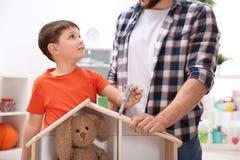 Mann und sein Kind, die Erbauer mit hölzernem Puppenhaus spielen lizenzfreies stockbild
