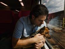 Mann und sein kleiner Mischzuchthund, die in einen Zug reisen stockfotografie