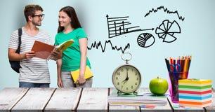 Mann und Studentinnen mit Büchern am Schreibtisch gegen Grafiken Lizenzfreies Stockfoto