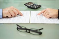 Mann und und Frau lesen langsam Versicherungspolice stockfotos