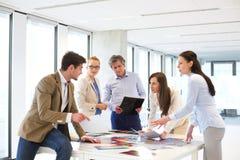 Mann und weibliche Designfachleute, die Diskussion bei Tisch im neuen Büro haben lizenzfreies stockfoto
