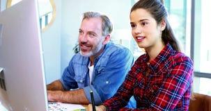 Mann und weibliche Grafikdesigner, die am Schreibtisch zusammenarbeiten stock footage