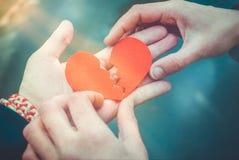 Mann und weibliche H?nde, die ein defektes Herz reparieren Scheidungskonzept Zu k?ssen Mann und Frau ungef?hr lizenzfreie stockbilder
