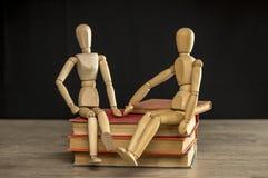 Mann und weibliche hölzerne Mannequins, die auf Büchern sitzen stockfoto