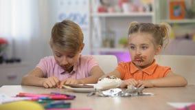Mann und weibliche Kinder geschmiert mit sitzender Tabelle der Schokolade, schädliche Nahrungsmittelkrankheit stock video