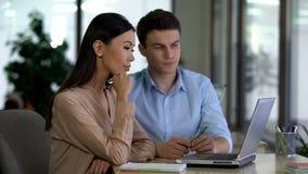 Mann und weibliche Kollegen, die Laptop im Büro, zusammenarbeitend Projekt betrachten stockfoto