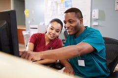 Mann und weibliche Krankenschwester-Working At Nurses-Station Lizenzfreies Stockfoto