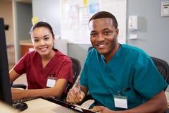 Mann und weibliche Krankenschwester-Working At Nurses-Station stockfotografie