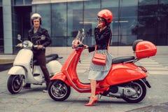 Mann und weibliches, Spaß auf moto Rollern habend Stockbilder
