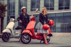 Mann und weibliches, Spaß auf moto Rollern habend Stockbild