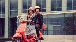Mann und weibliches, Spaß auf moto Rollern habend Stockfotos