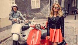 Mann und weibliches, Spaß auf moto Rollern habend Lizenzfreie Stockbilder