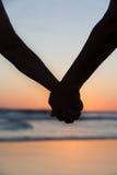 Junge Paare, die Hände auf dem Seestrand am Sonnenuntergang halten Stockbilder