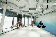 Mann und zwei Frauen, die Stille beim Üben von Luftyoga genießen lizenzfreie stockbilder